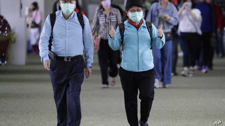 A passenger wearing a mask gestures as they arrive at Manila's international airport, Philippines, Thursday, Jan. 23, 2020. The…