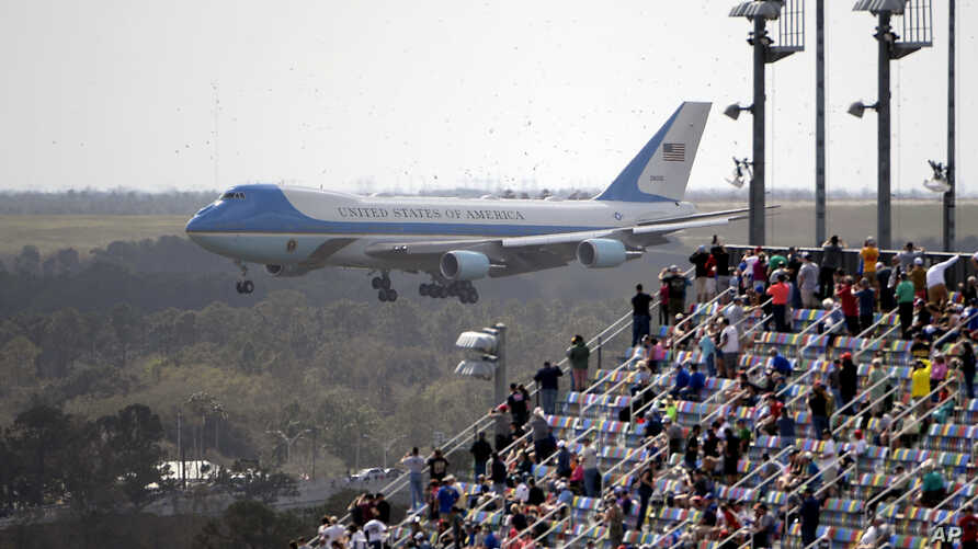 Fans watch from the grandstands as Air Force One, carrying President Donald Trump, prepares to land at Daytona International…