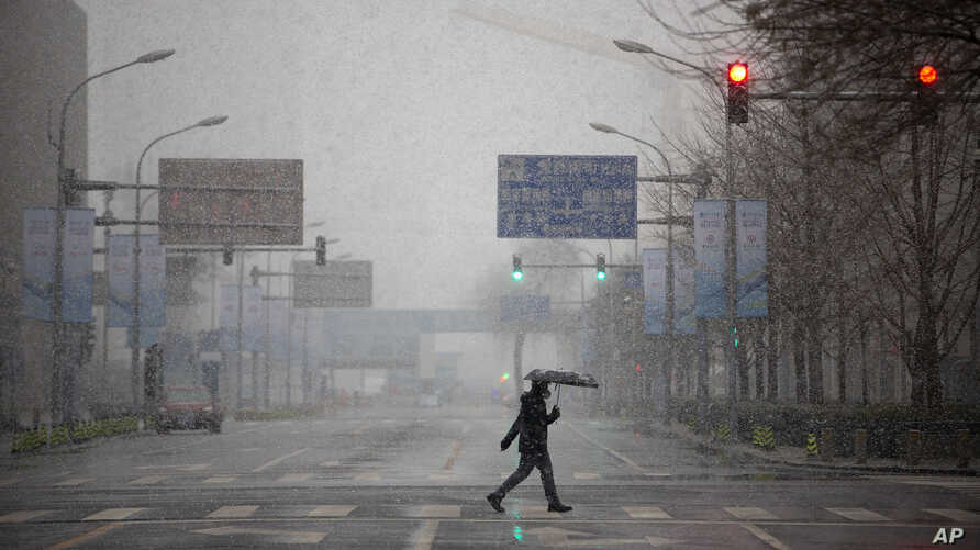 A man wears a mask as he walks across an empty intersection during the morning rush hour as snow falls in Beijing, Friday, Feb…