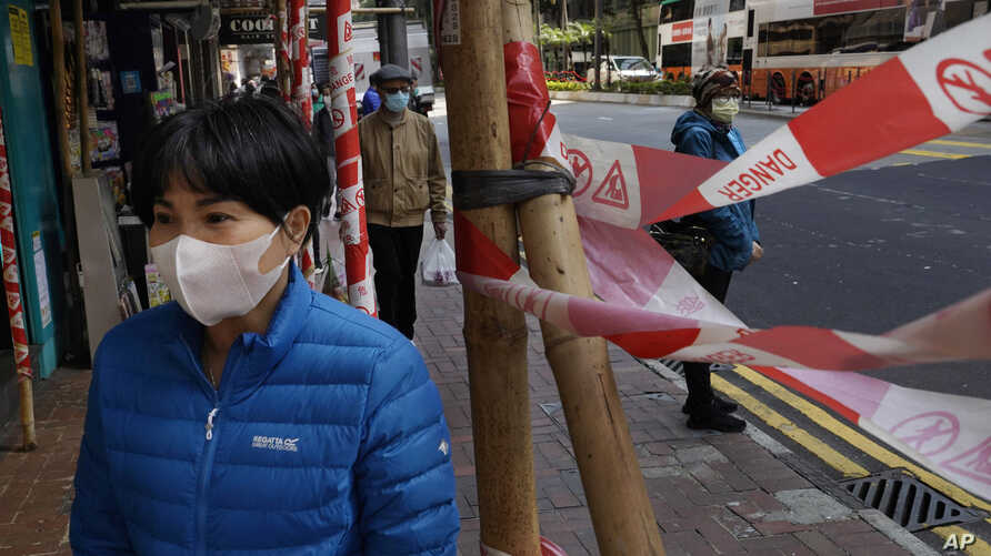 A woman wearing face mask walks on a street in Hong Kong Tuesday, Feb. 18, 2020. COVID-19 viral illness has sickened tens of…