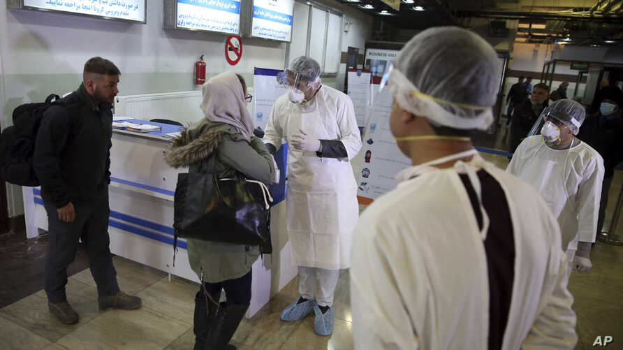 Afghan health workers wearing protective gear speak with passengers who arrived from China during a screening process for…