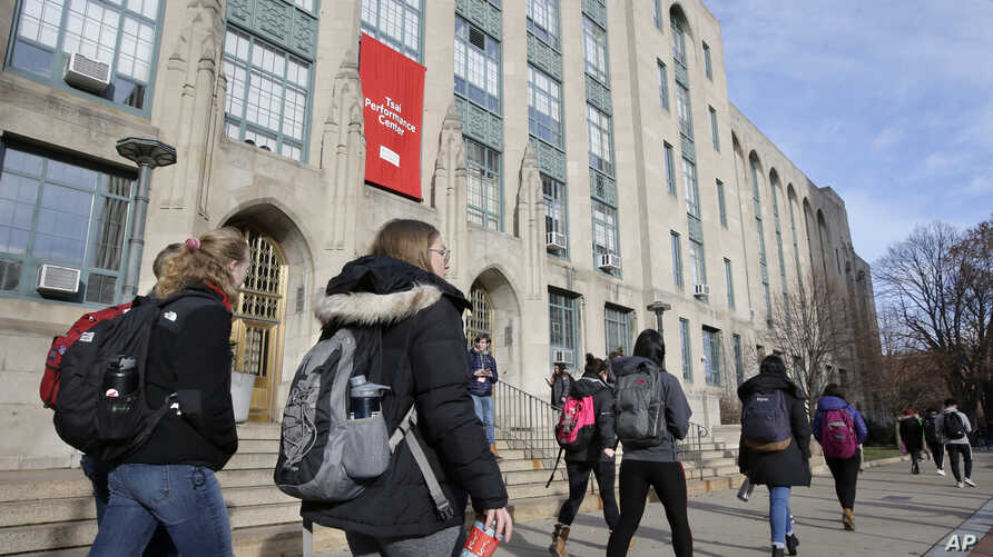 FILE - Students and passers-by walk past an entrance to Boston University College of Arts and Sciences, in Boston, Massachusetts, Nov. 29, 2018.