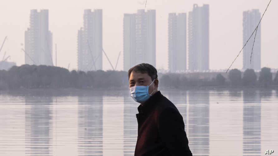 FILE - In this Jan. 30, 2020 file photo, a man wears a face mask as he stands along the waterfront in Wuhan in central China's…