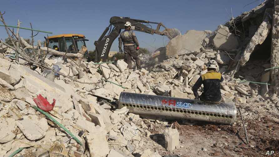Syrian rescuers search for victim between rubble of a destroyed house after deadly airstrikes at the northern town of Sarmin,…