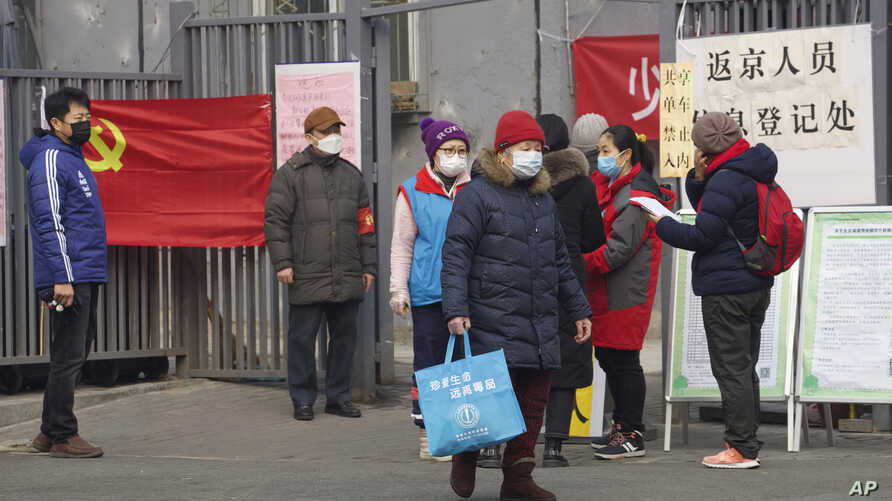 """Residents wait to enter a checkpoint with a sign which reads """"Returnees to Beijing registration point"""" in Beijing, China…"""
