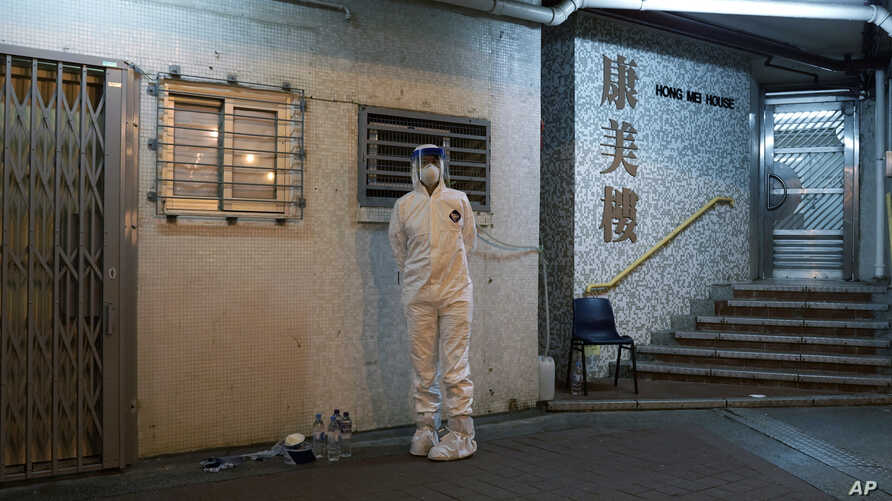 A personnel wearing protective suit waits near a block's entrance at the Cheung Hong Estate, a public housing estate during…