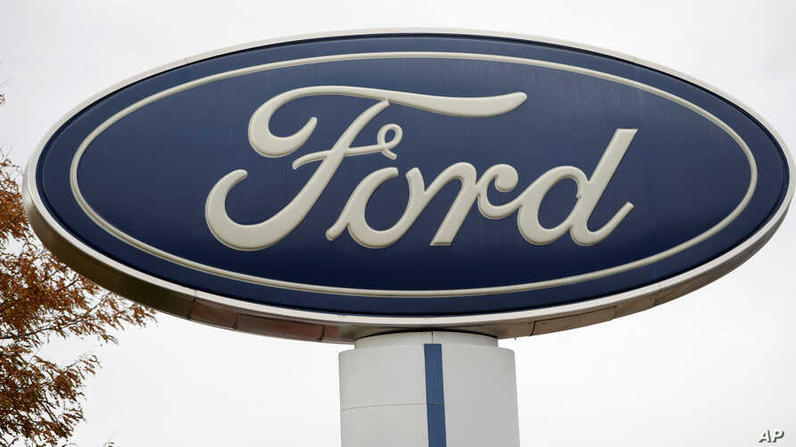 FILE - In this Oct. 20, 2019, file photo, the company logo stands over a long row of unsold vehicles at a Ford dealership in…