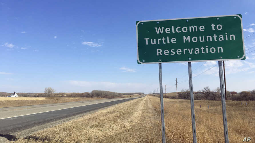 File - In this Wednesday, Oct. 24, 2018, file photo, a sign to the Turtle Mountain Reservation of Native Americans in North…