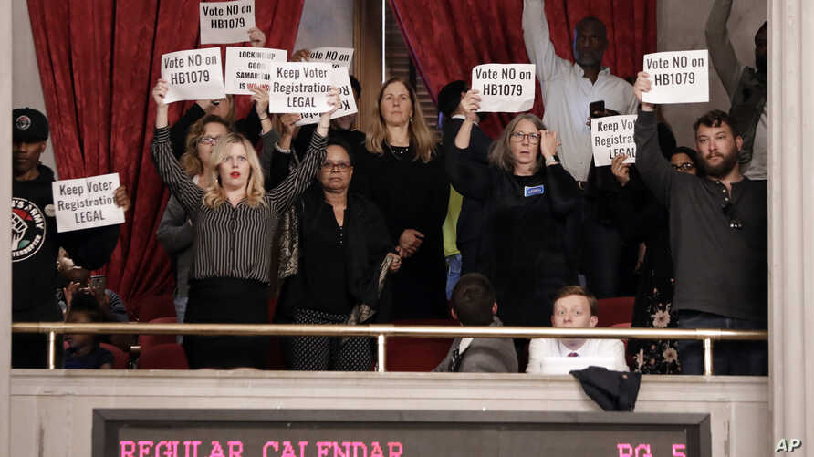 Protesters hold up signs in the House gallery opposing a bill pushed by the Tennessee Secretary of State that would impose new…