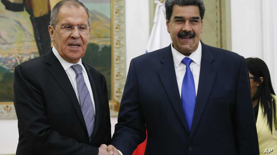 Venezuelan President Nicolas Maduro, right, shakes hands with Russia's Foreign Minister Sergey Lavrov during a photo…