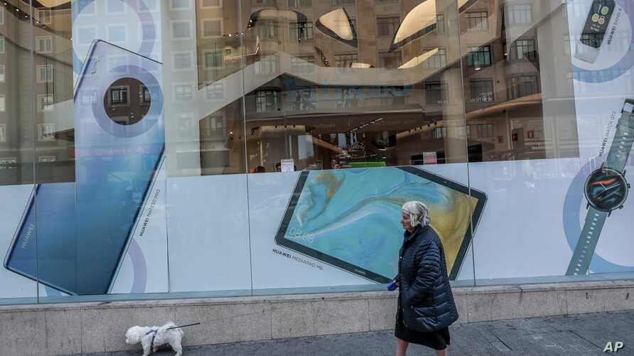 A woman and her dog walk past a Huawei shop in Madrid, Spain, Thursday, Feb. 20, 2020. The top U.S. diplomat for cybersecurity…