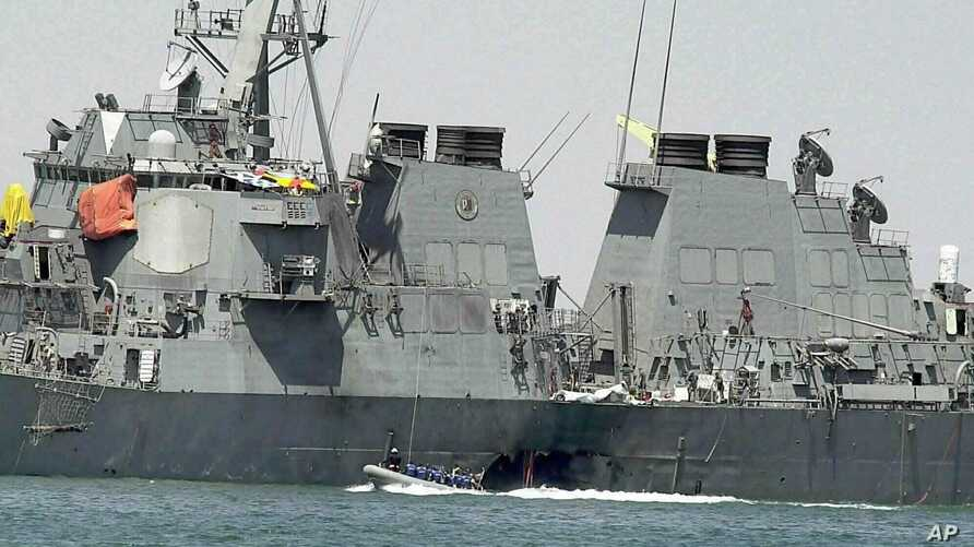 FILE - In this Oct. 15, 2000 file photo, experts in a speed boat examine the damaged hull of the USS Cole at the Yemeni port of…