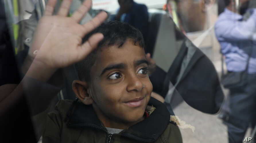 A Yemeni boy waves from inside a bus before boarding a United Nations plane at Sanaa International airport, Yemen, Monday, Feb…