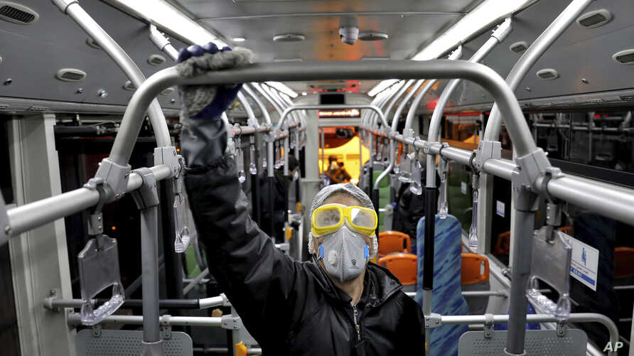 A worker disinfects a public bus against coronavirus in Tehran, Iran, in early morning of Wednesday, Feb. 26, 2020. Iran's…