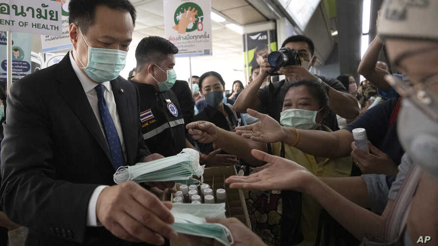 Thailand's Public Health Minister Anutin Charnvirakul, left, distributes masks to commuters during a campaign for wearing masks…