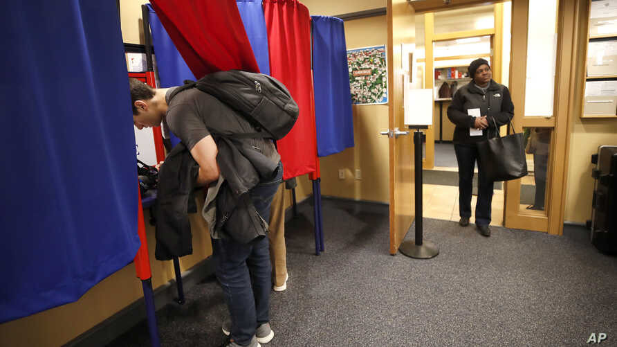 A voter waits her turn, Monday, Feb. 24, 2020, as others vote at the Cambridge City Hall annex, on the first morning of early…
