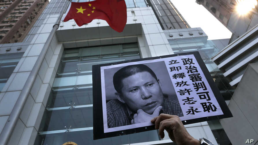 A placard with a photo of legal scholar Xu Zhiyong is raised by a demonstrator protesting against a Chinese court's decision to…