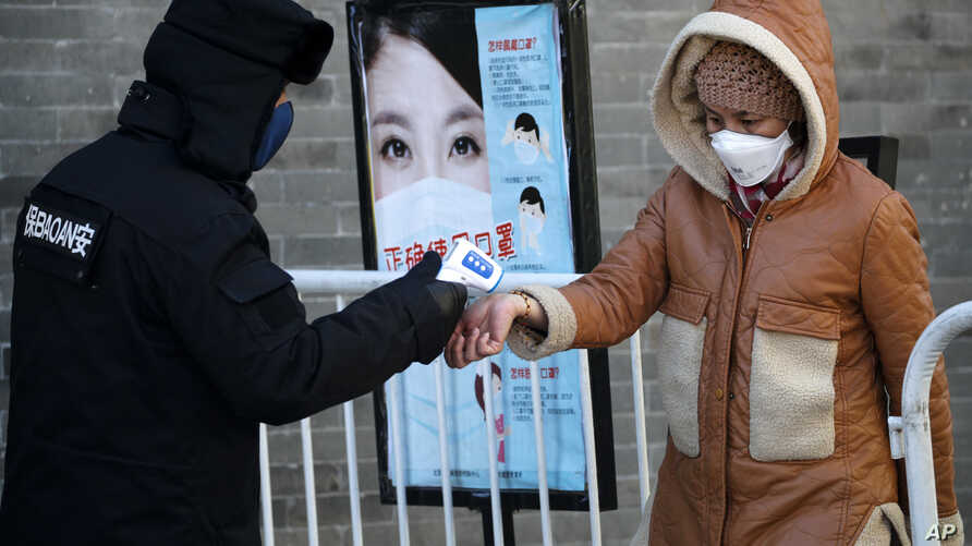 A woman wearing a protective face mask receives a temperature check from a security guard as she enters Qianmen Street, a popular tourist spot, in Beijing, Feb. 16, 2020.