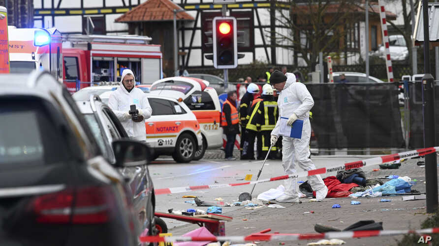 Police and rescue workers stand next to the scene of the accident with a car that is said to have crashed into a carnival…