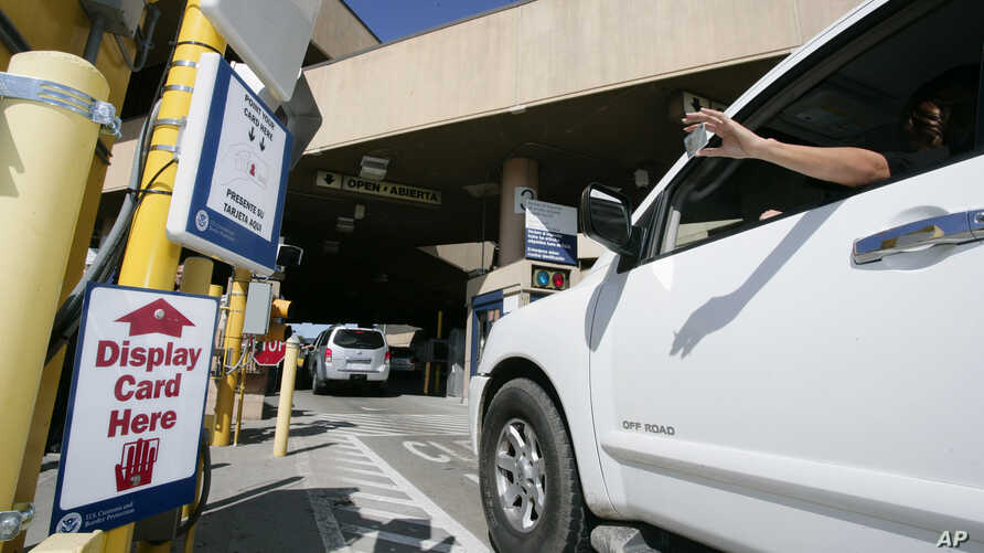 A driver holds up a new radio frequency enhanced U.S. border crossing card as she crosses the U.S.-Mexico border at the San…