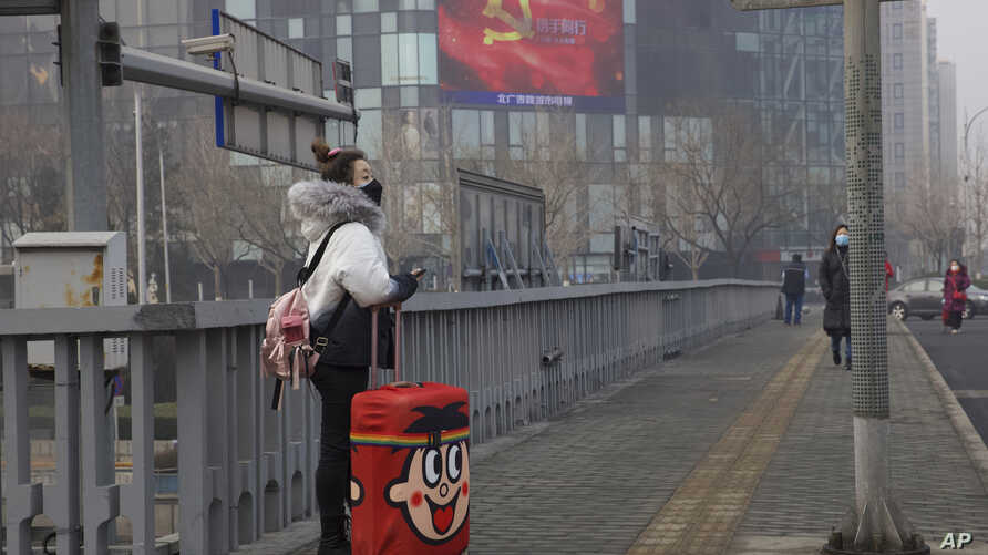 A traveler stands on a bridge near a display showing government propaganda in the fight against the COVID-19 viral illness in…