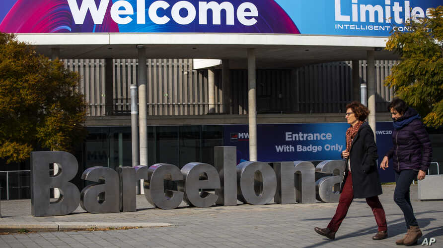 People walk past posters announcing the Mobile World Congress 2020 in a conference venue in Barcelona, Spain, Tuesday, Feb. 11,…