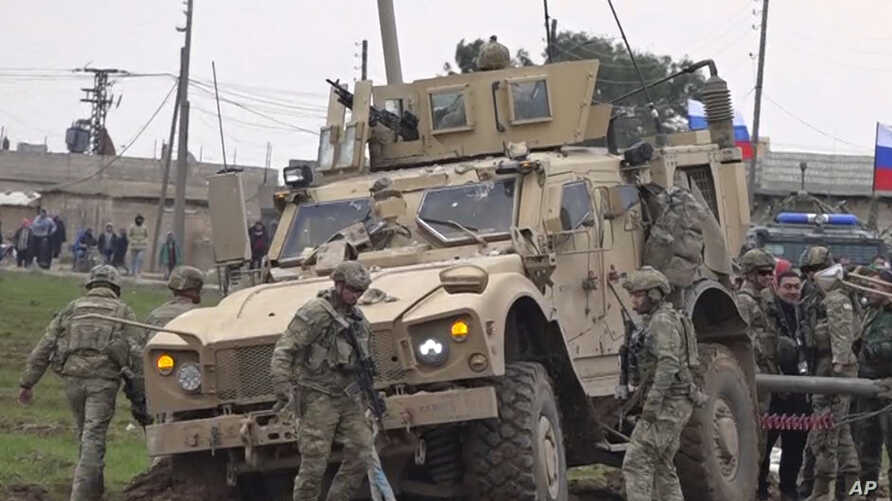 In this frame grab from video, people and soldiers gathering next to an American military convoy stuck in the village of…