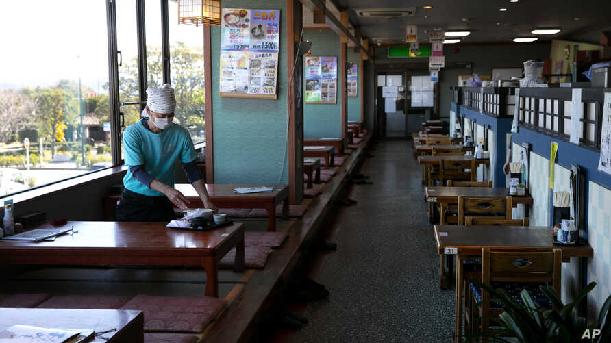 A server with a mask cleans a table at a restaurant in Fujisawa, Japan, Thursday, Feb. 27, 2020. According to local businesses…