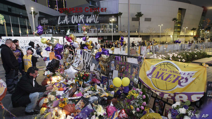 FILE - In this Feb. 2, 2020, file photo, fans gather at a memorial for Kobe Bryant in front of Staples Center in Los Angeles. A…