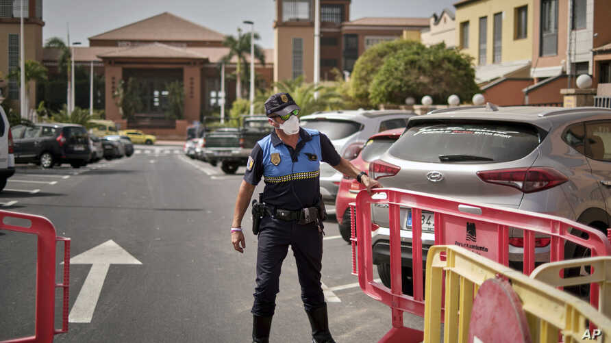 A Spanish police officer sets a barrier blocking the access to the H10 Costa Adeje Palace hotel in Tenerife, Canary Island,…
