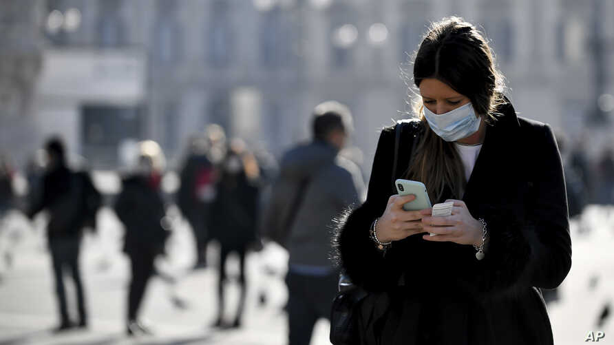 A woman wearing a sanitary mask looks at her phone in Milan, Italy, Monday, Feb. 24, 2020. At least 190 people in Italy's north…