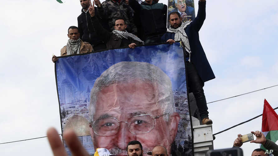 Protestors wave Palestinian flags during a rally supporting Palestinian President Mahmoud Abbas, shown in banner, and against…