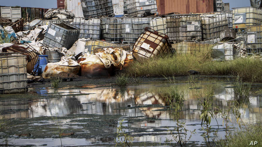 In this photo taken Monday, Oct. 1, 2018, containers used for hazardous chemicals lie exposed and piled up at a junkyard run by…