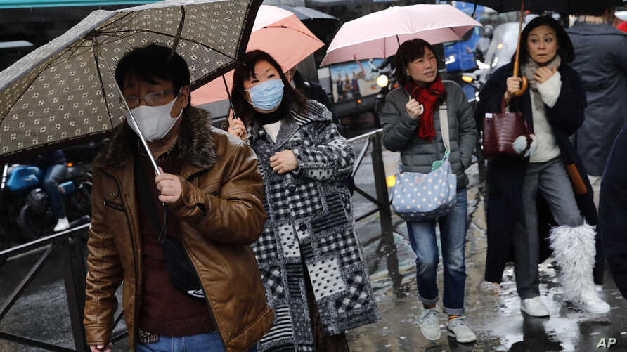 People, some wearing a mask, walk in Paris, Monday, March 2, 2020. The French government has banned any indoor gatherings…