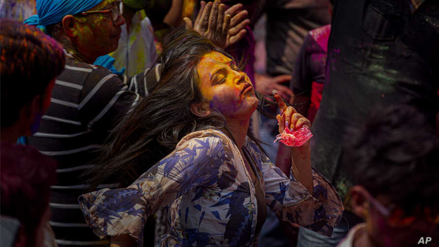 Indians dance and throw colored powder during Holi festival celebrations in Gauhati, India, Tuesday, March 10, 2020. The…