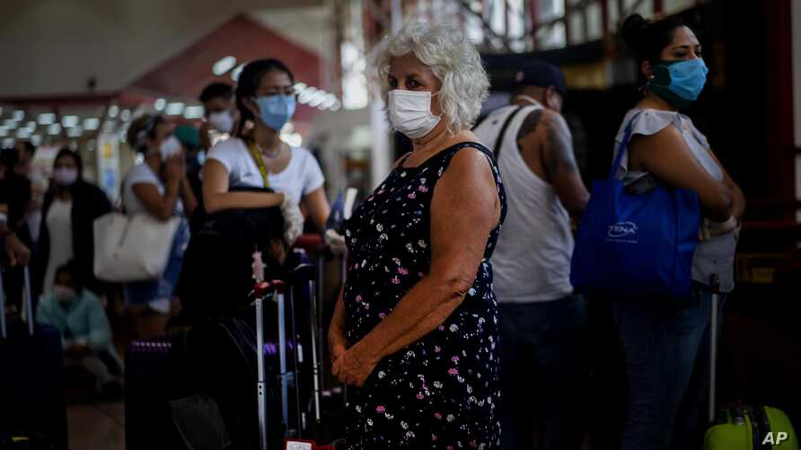 Tourists wearing masks as a precaution against the spread of the new coronavirus, wait in line for their flights home, at the…