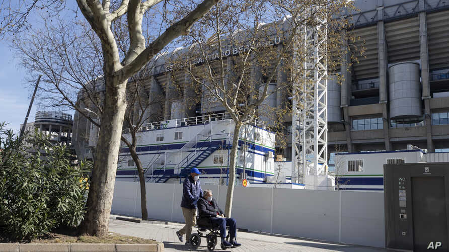 A man is pushed in the wheelchair while wearing protective masks near Real Madrid's Santiago Bernabeu stadium in Madrid, Spain,…
