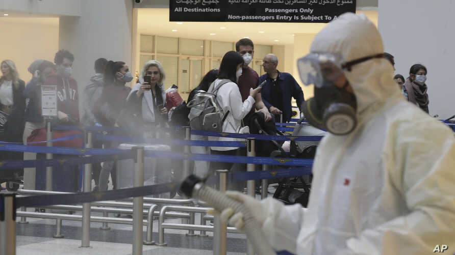 Passengers line up as workers wearing protective gear spray disinfectant as a precaution against the coronavirus outbreak, in…