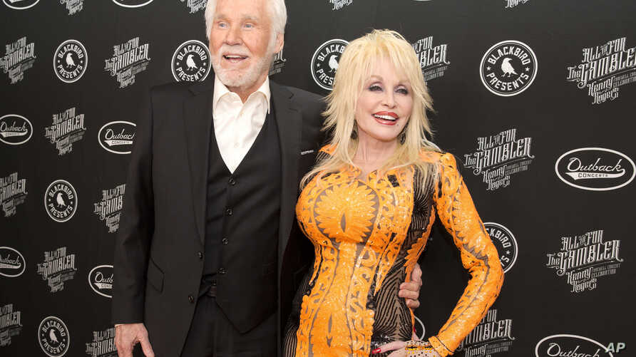 "Kenny Rogers, left, and Dolly Parton walk the red carpet of the ""All In For The Gambler: Kenny Rogers' Farewell Concert…"