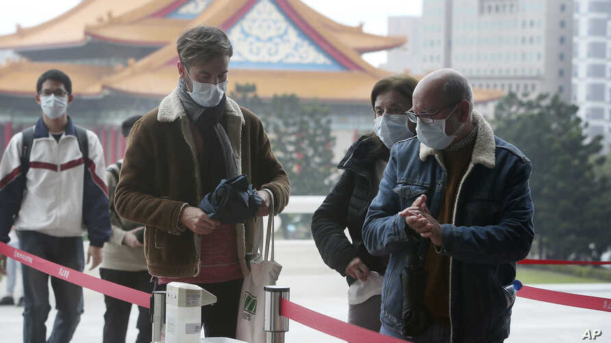 People wear face masks to protect against the spread of the new coronavirus as they visit the Chiang Kai-shek Memorial Hall in…