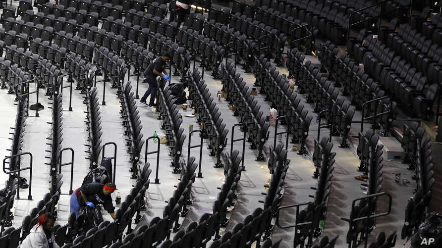 Workers clean the Wells Fargo Center after an NBA basketball game between the Philadelphia 76ers and the Detroit Pistons,…