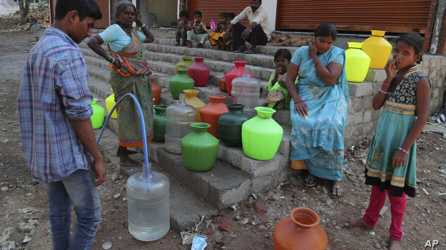 Residents of a poor neighborhood collect potable water from a public tap in Hyderabad, India, Wednesday, March 18, 2020…
