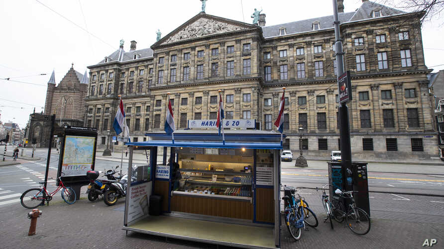 An empty herring stand and deserted streets around noon, outside the Royal Palace, rear, in the center of Amsterdam,…