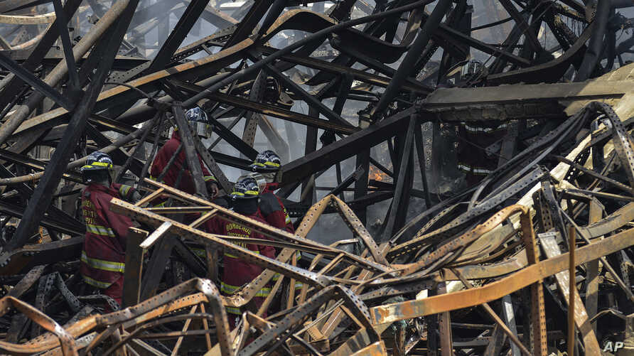 Firefighters work in the aftermath of a fire at a warehouse of the National Electoral Council where tens of thousands of voting…