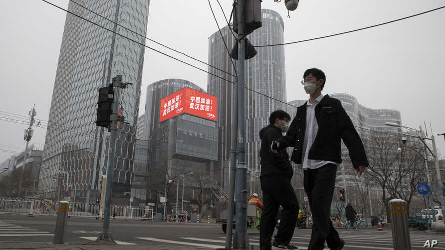 "Residents walk past a retail and office district with a screen showing propaganda which reads ""Go China! Go Wuhan"" as…"