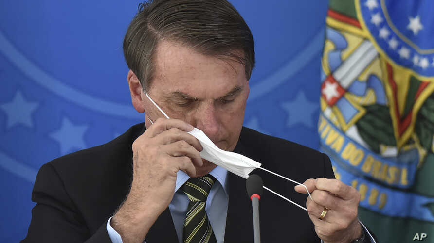 Brazil's President Jair Bolsonaro puts on a mask during a press conference on the new coronavirus at the Planalto Presidential…