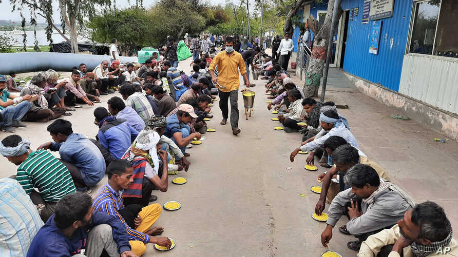 Homeless and impoverished Indians receive food at a government shelter in New Delhi, India, Thursday, March 26, 2020. Some of…