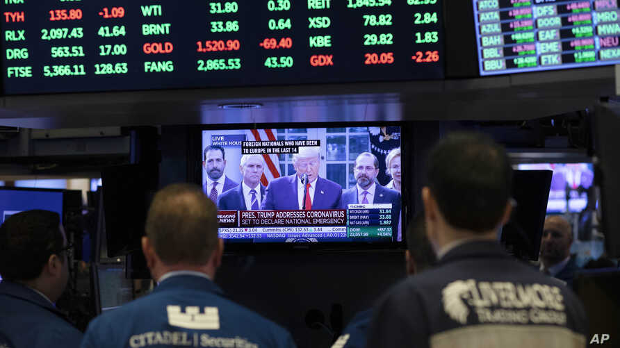 Traders listen at the New York Stock Exchange to President Donald Trump's televised speech from the White House, Friday, March…