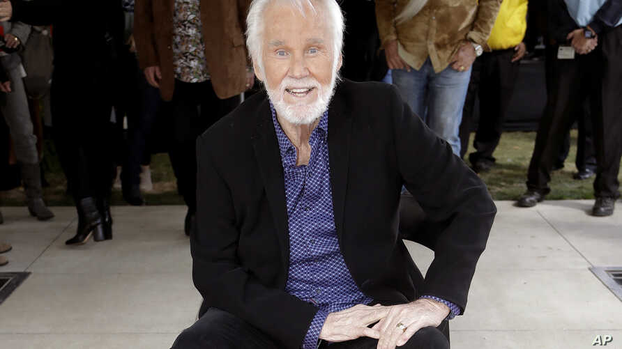 FILE - In this Oct. 24, 2017 file photo, Kenny Rogers poses with his star on the Music City Walk of Fame in Nashville, Tenn…