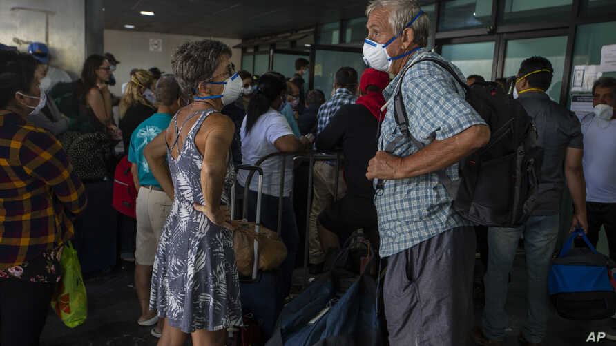 Travelers wait for a charter flight coordinated by the U.S. embassy at the La Aurora airport in Guatemala City, Tuesday, March…